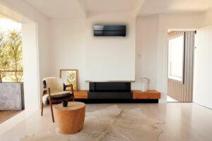 Moderne stue med varme fargetoner, hvit åpen murpeis og lekker sort varmepumpe under himling.