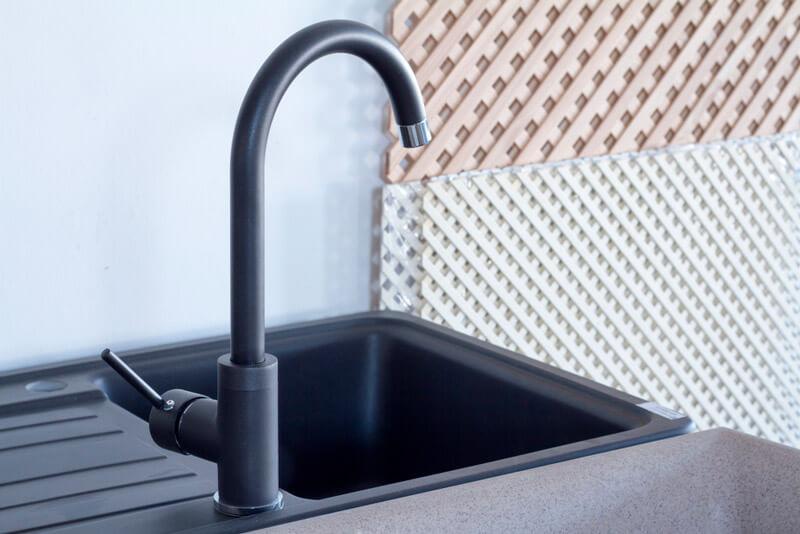 Sort vannkran på kjøkkenbenk