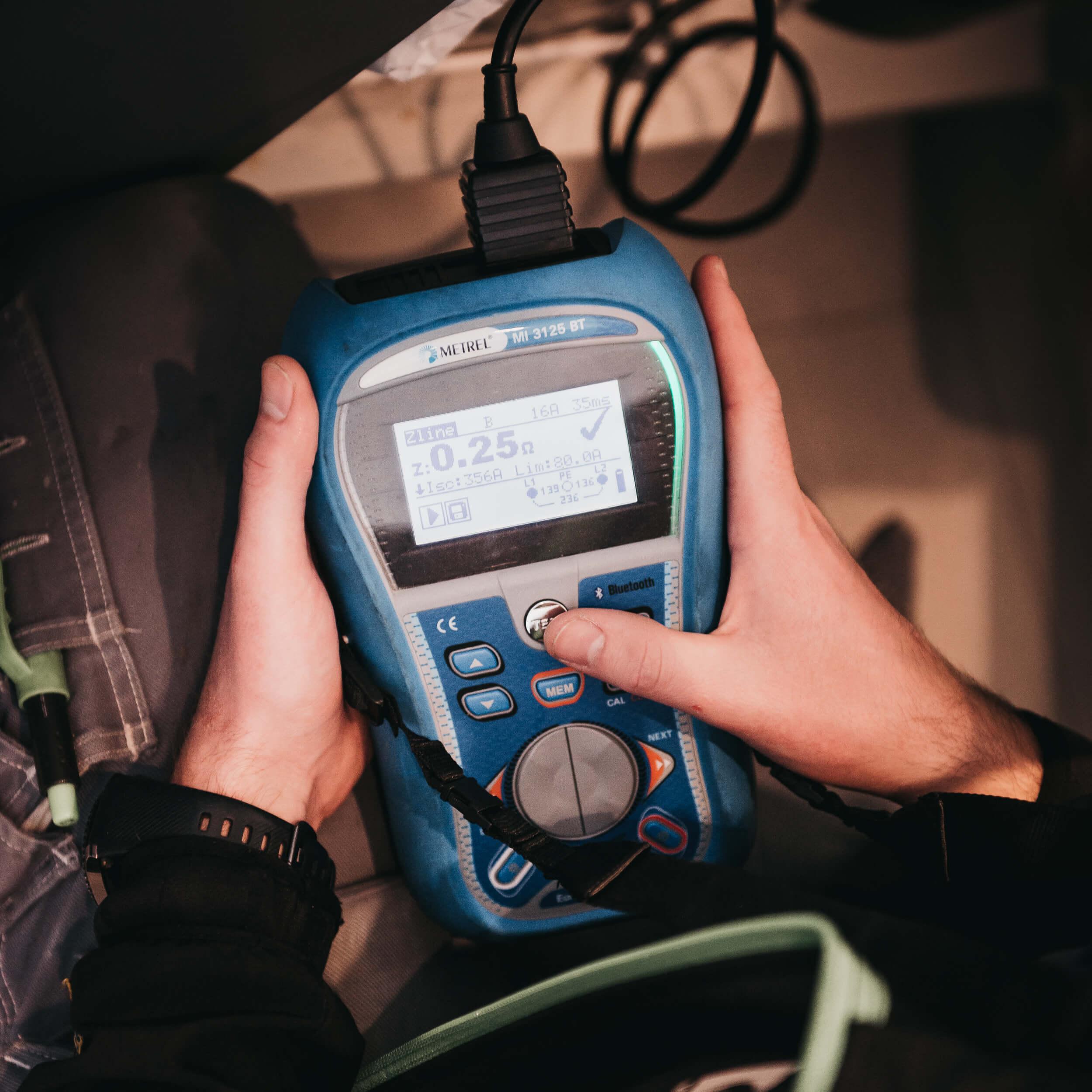 Elektriker bruker strøm-måler til å kontrollere stikkontakt.