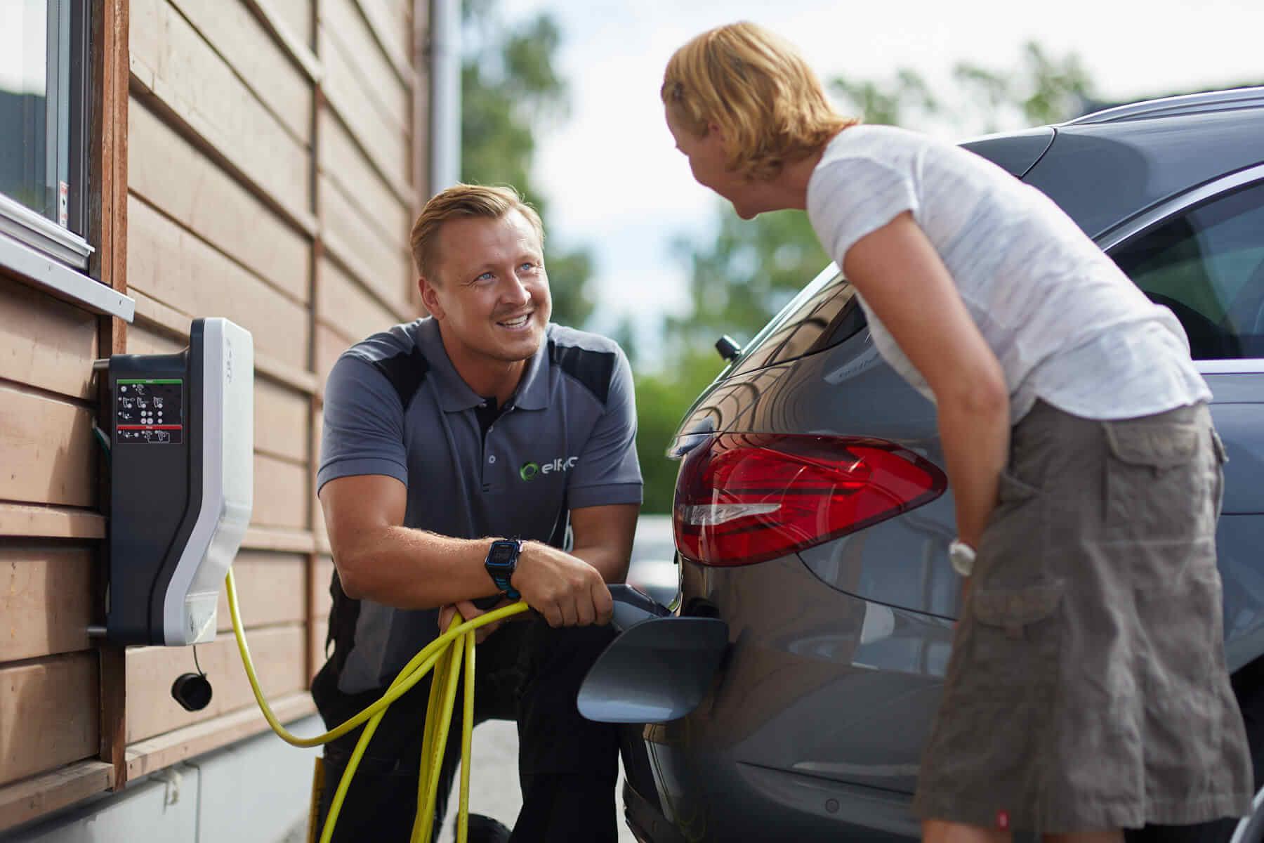 Elfag elektriker og kunde med elbil-lader og bil.