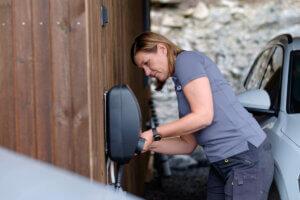 elektriker kvinne fra elfag monterer elbillader på en vegg