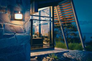 Veggmontert lampe lyser opp idyllisk hus en høstkveld.