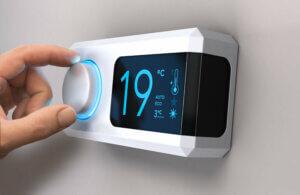 En hånd som justerer en veggmontert termostat