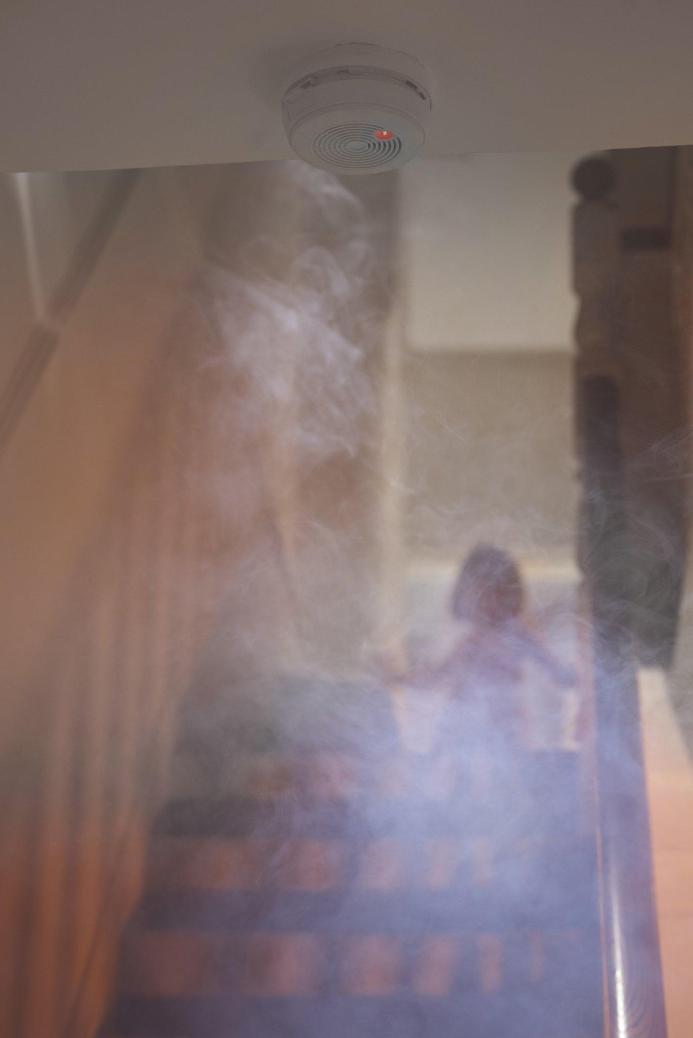 barn øverst i trapp i røykfylt rom.