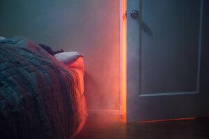 røykfylt soverom med person i seng.