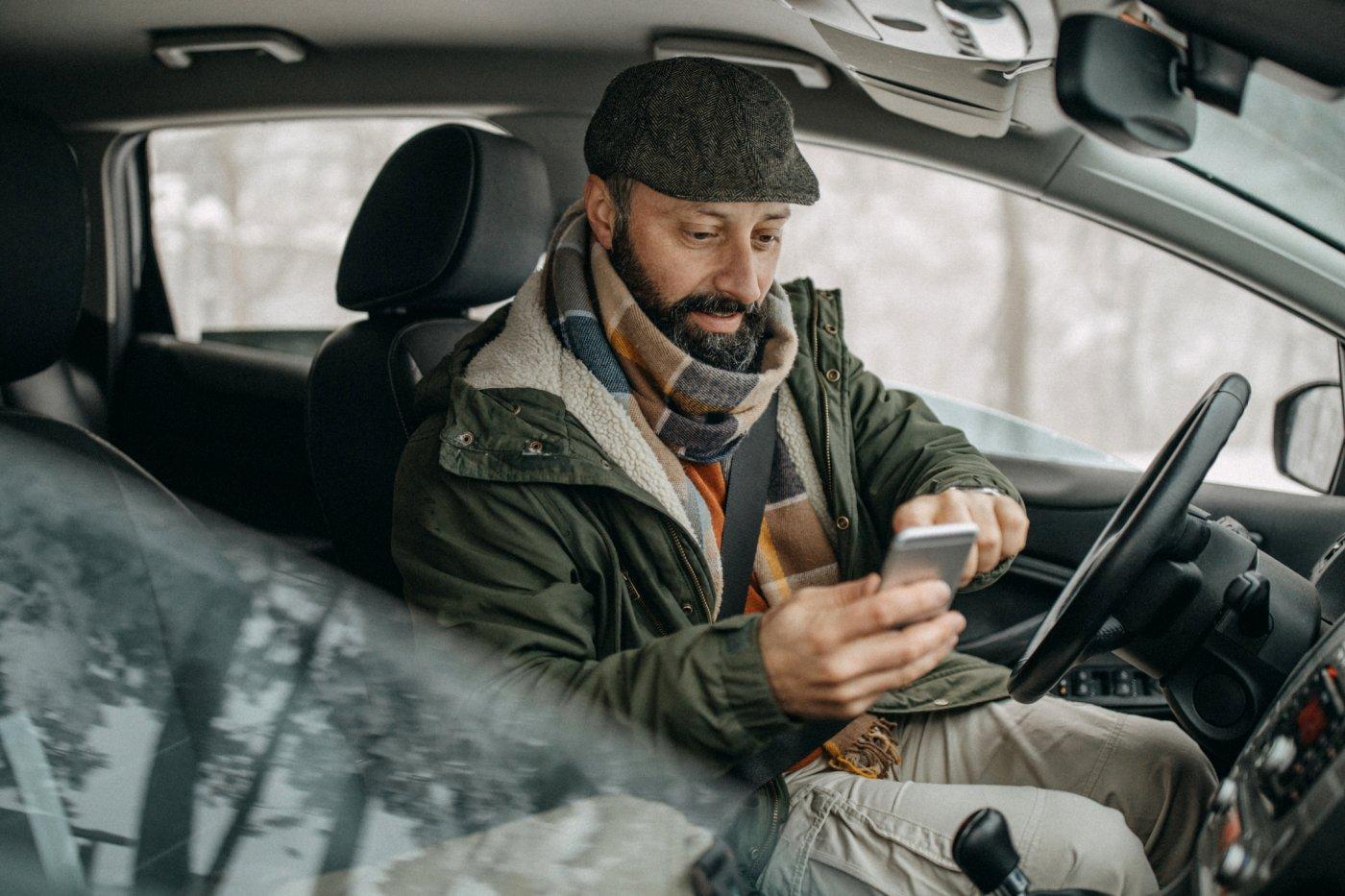 en mann med hatt og jakke sitter i bilen og taster på mobilen