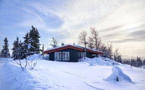 en hytte i vinterlandskap med mye snø rundt