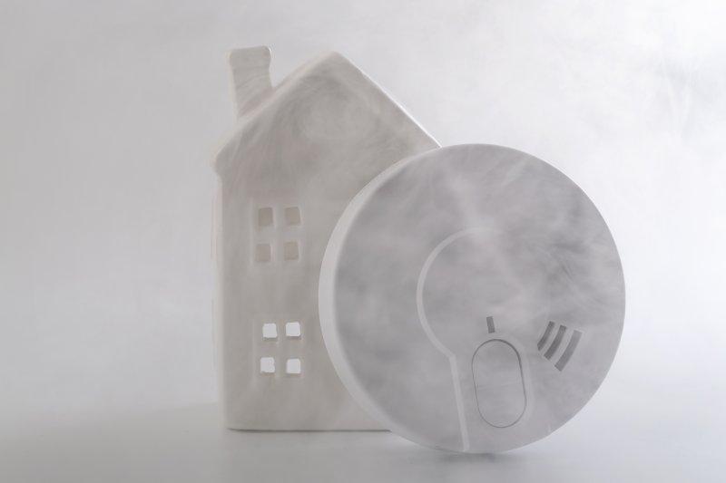 røykvarsler stilt opp inntil et miniatyrhus dekket av røyk.