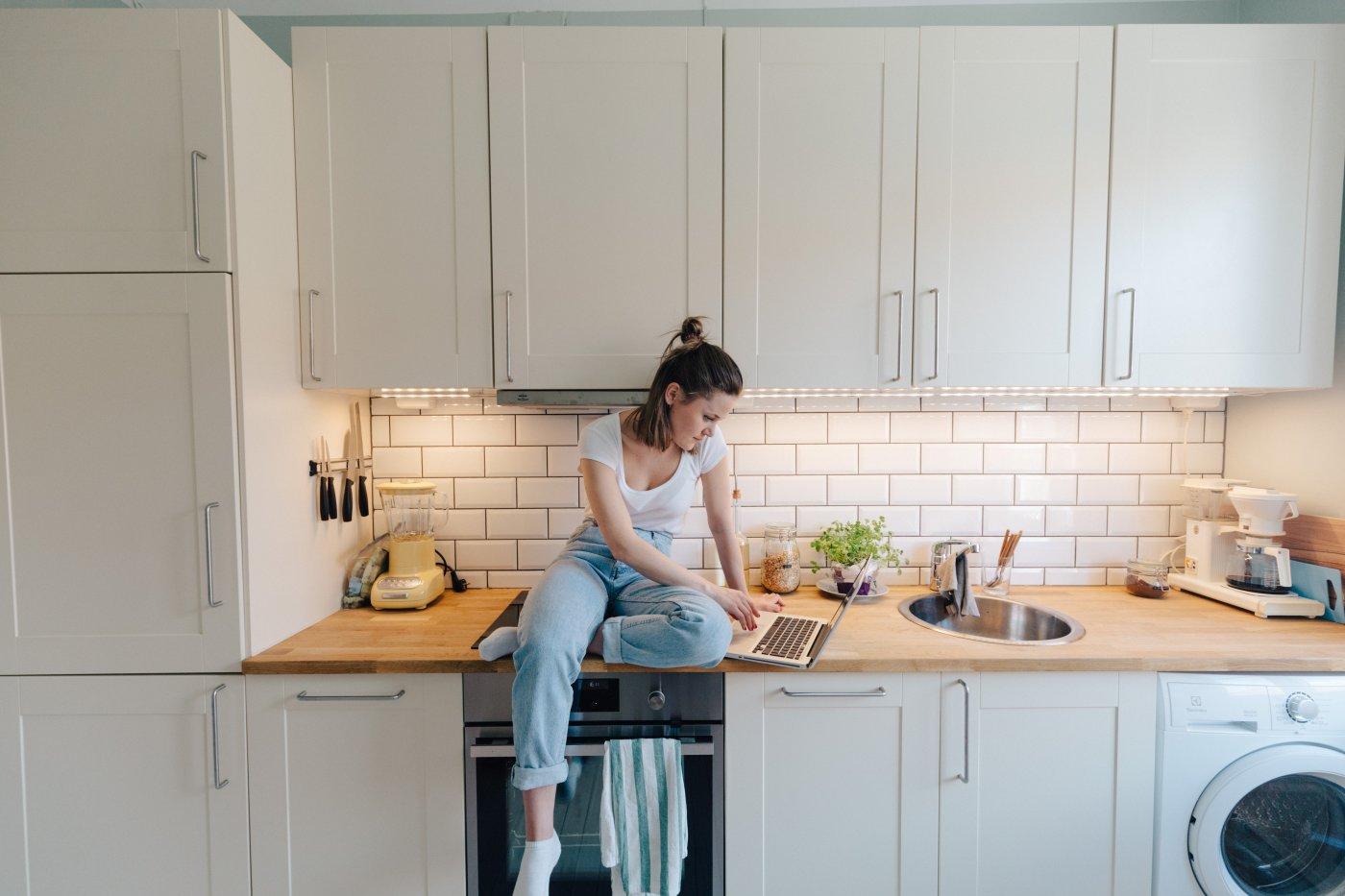 kvinne sitter på data på kjøkkenbenk