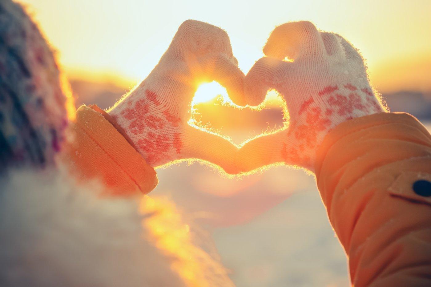 sollys gjennom hjerteformet hånd om vinteren