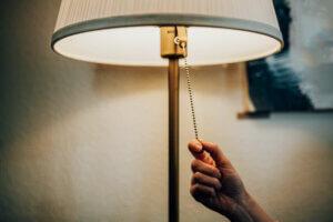 hånd skrur av lys i stue