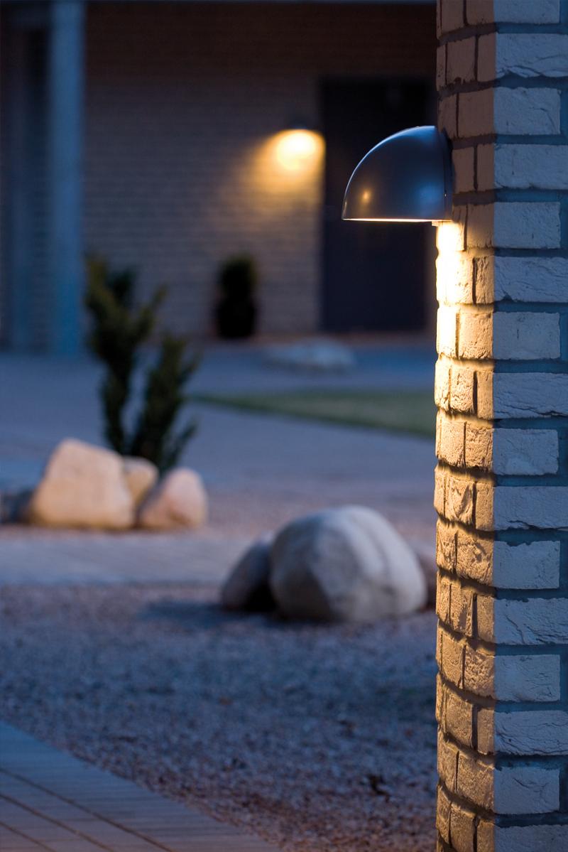 Vegglampe montert på murvegg for å lyse nedover.
