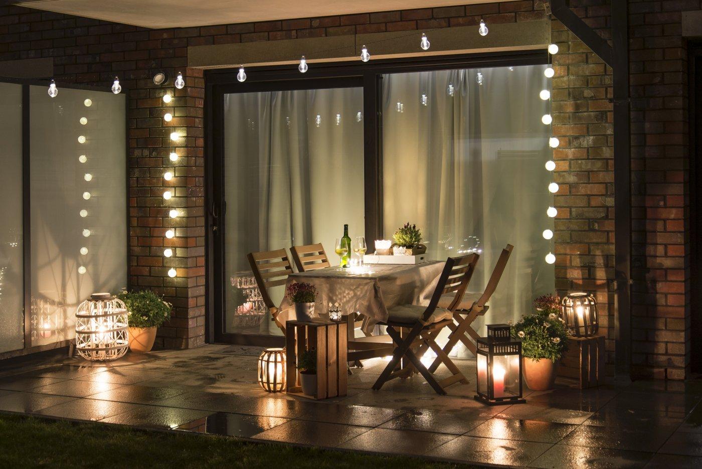 uteområde opplyst av happy lights og lyssatt bord og platting