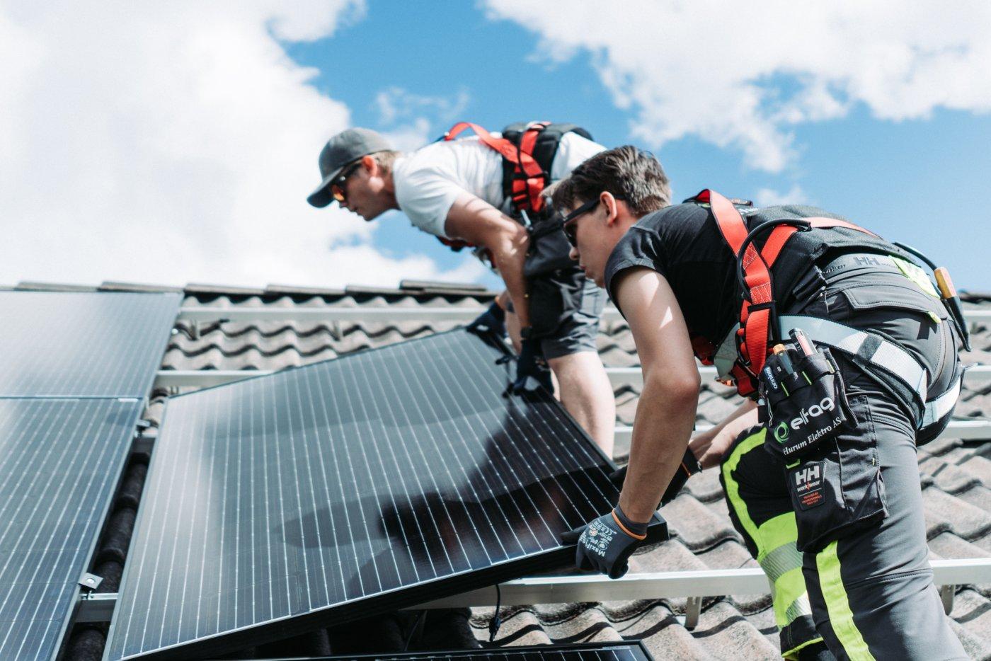 Nærbilde av to Elfagere som legger solcellepanel på tak.