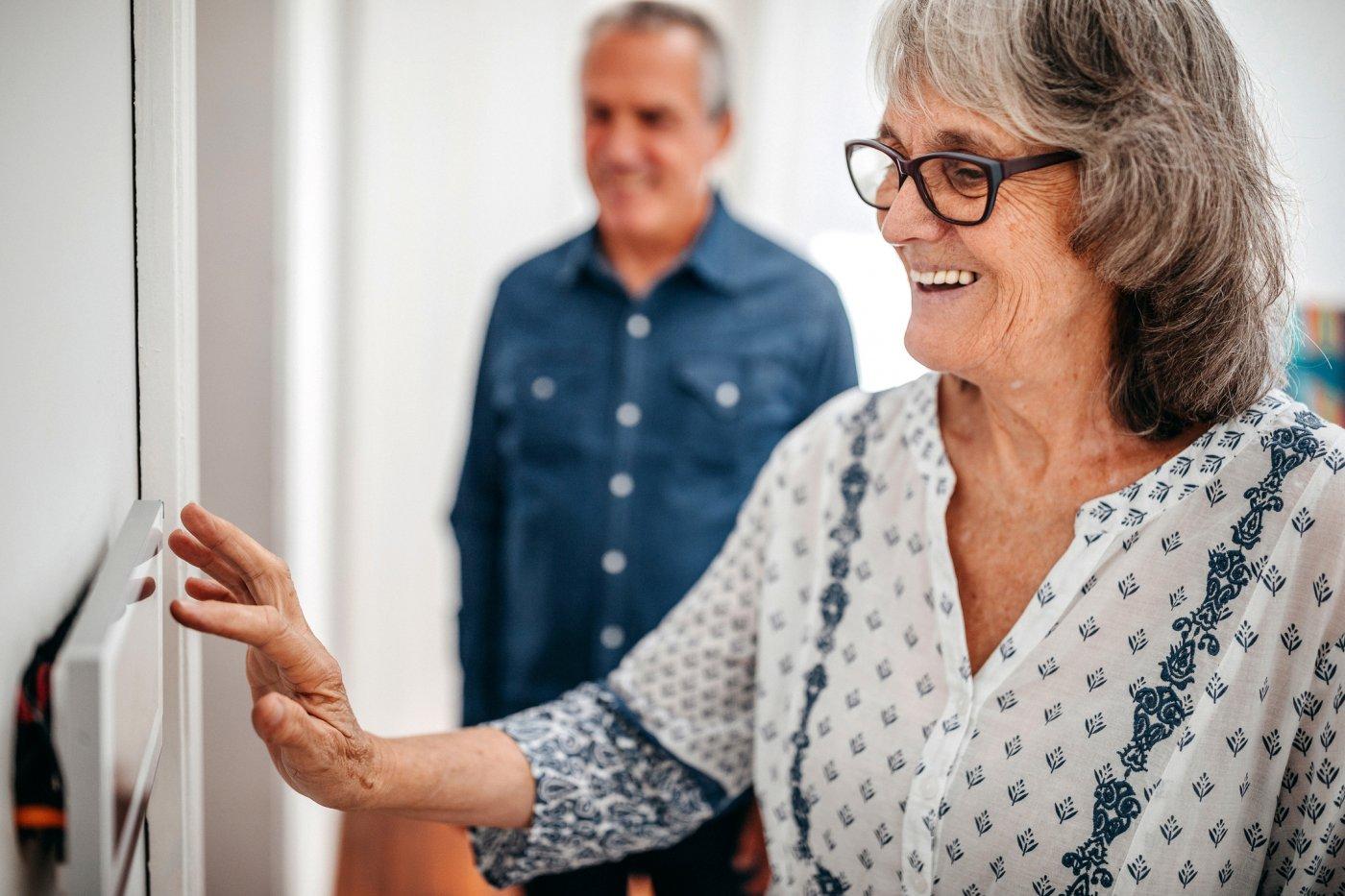 En eldre kvinne endrer innstillinger på et digitalt veggpanel.