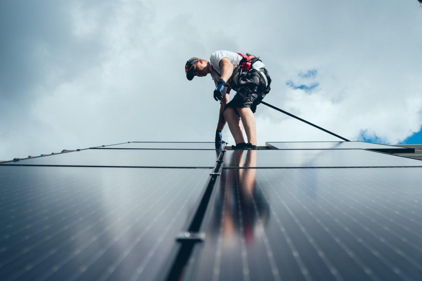 elfagelektriker på tak som monterer solcellepanel hos forbruker