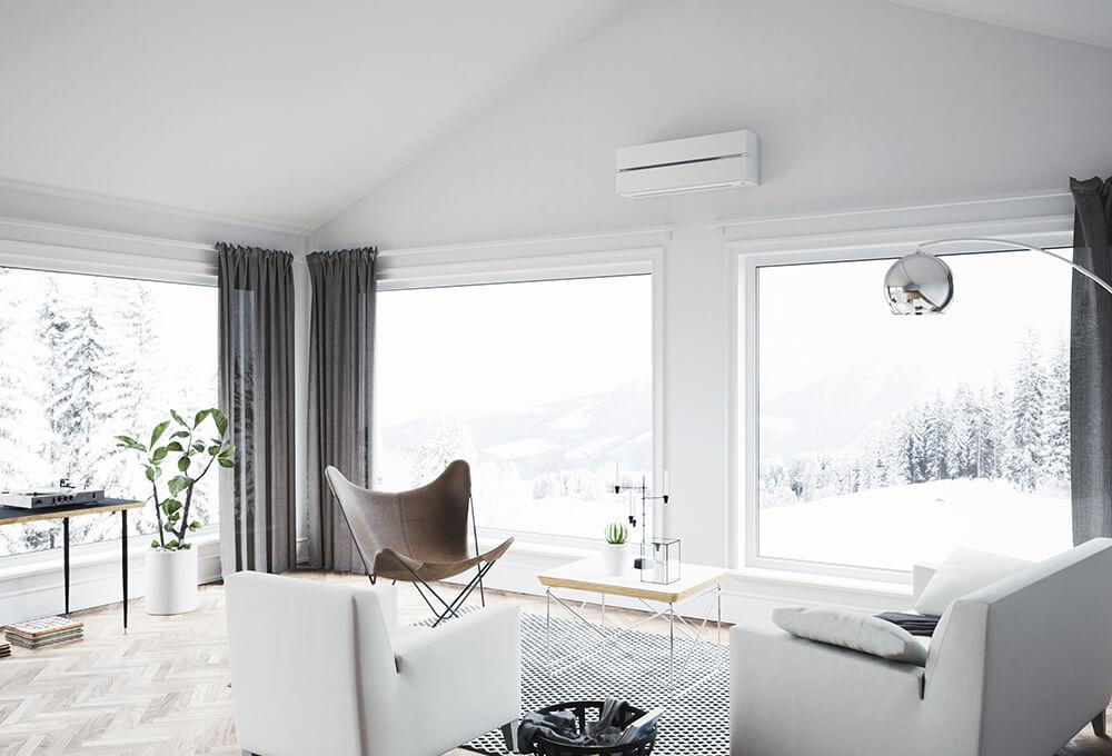 Hvit varmepumpe montert under himling i stor, lys stue med vinterlandskap utenfor.