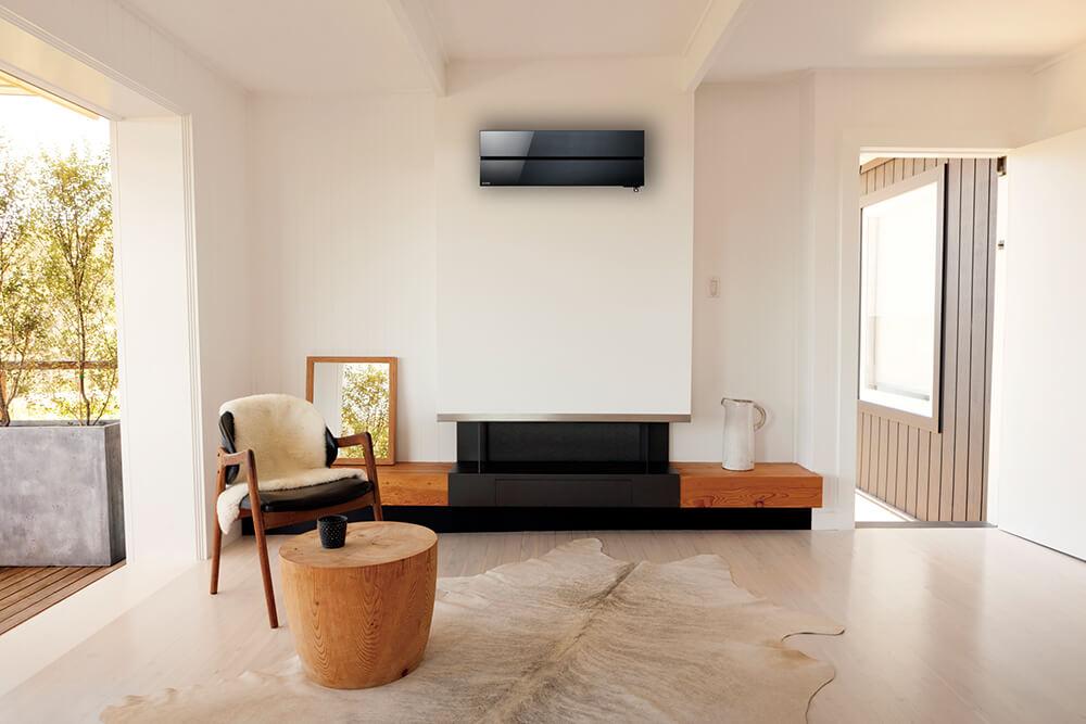 Sort varmepumpe montert under himling i moderne stue med peis.