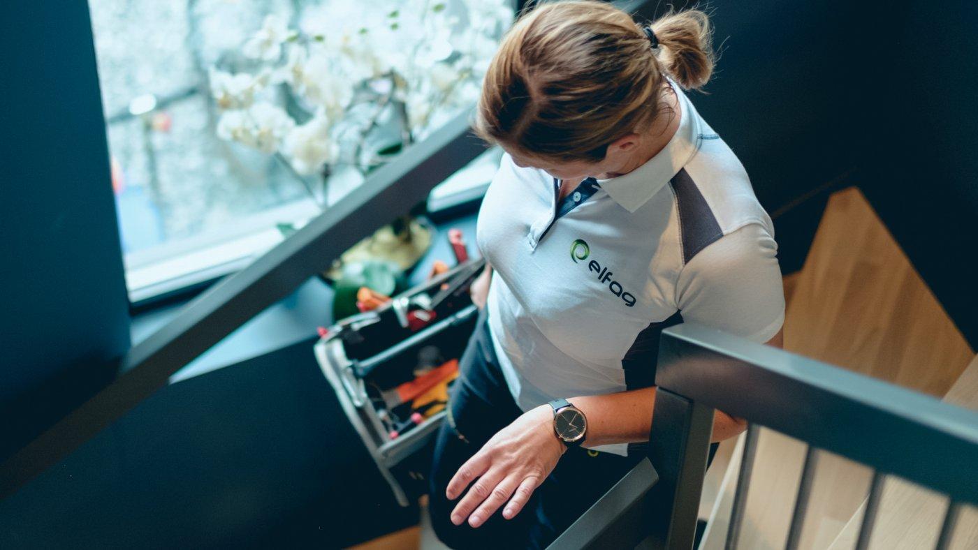 kvinnelig elektriker med Elfag t-skjorte, sett ovenfra, går nedover trappen med verktøykasse i hånden.