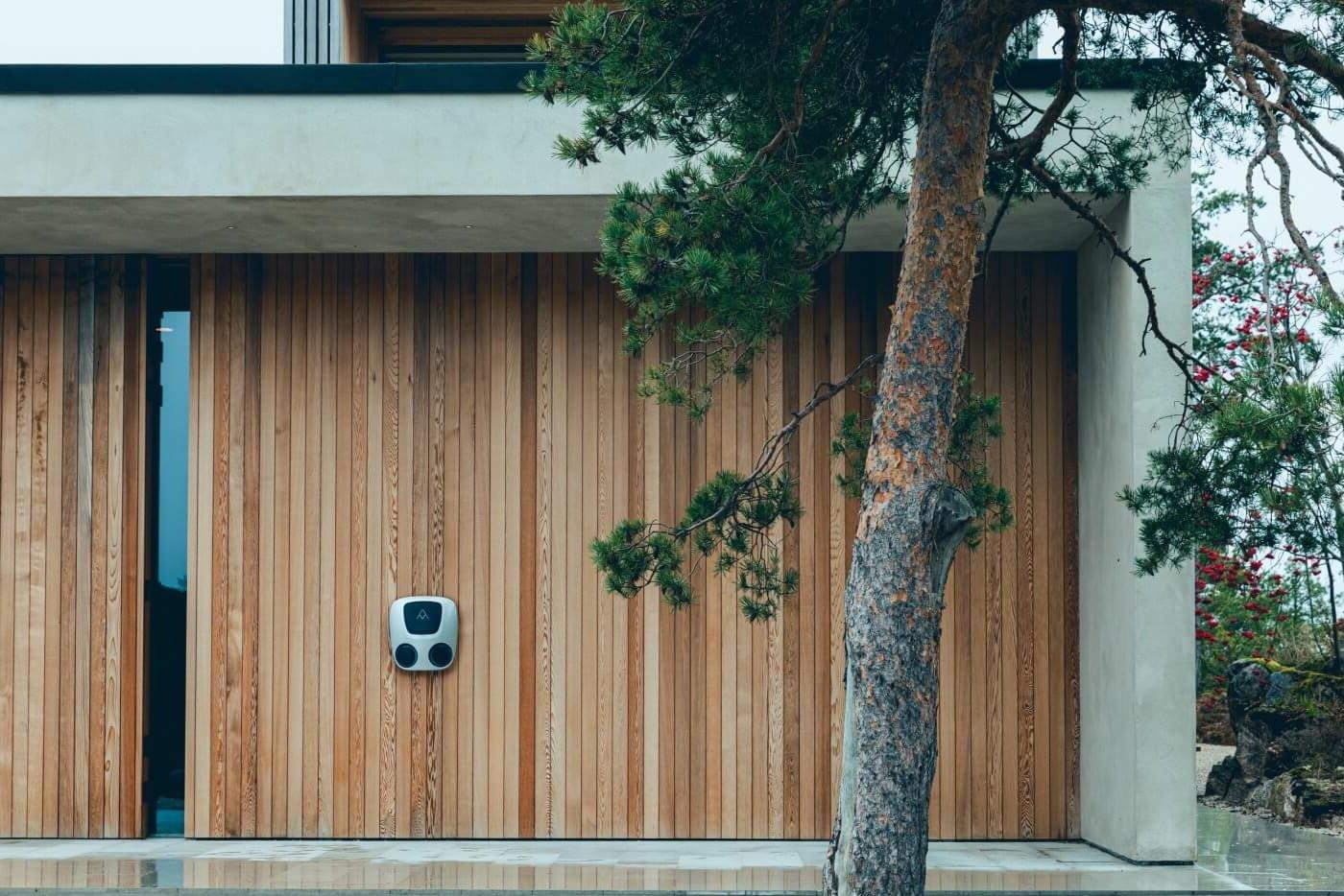 liten og kompakt elbillader med to uttak montert på moderne husvegg i treverk og betong med furutre i forgrunnen.