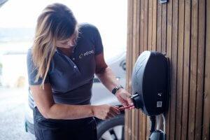 kvinnelig elektriker monterer sort elbillader på husvegg.