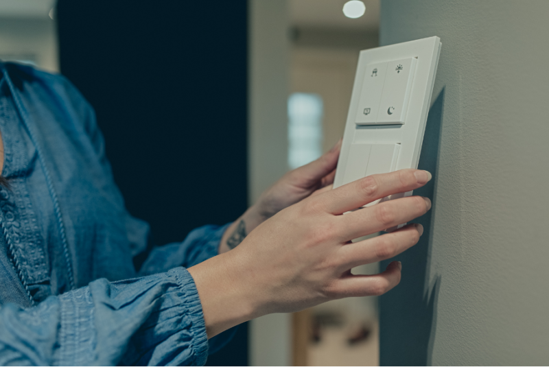 En dame plasserer en trådløs bryter på et tilfeldig sted på veggen.