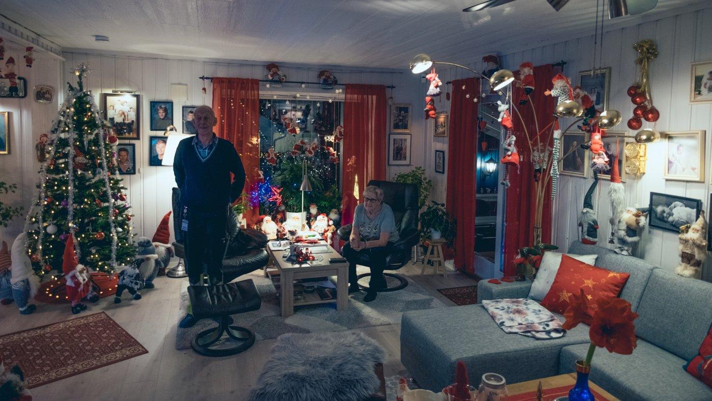 Stua er pyntet med røde gardiner, nisser og juletre. Tore og Bjørg står og sitter ved spisebordet i midten av bildet, med vinduet bak seg. Det er nisser i tak, på vegger og på alle hyller.