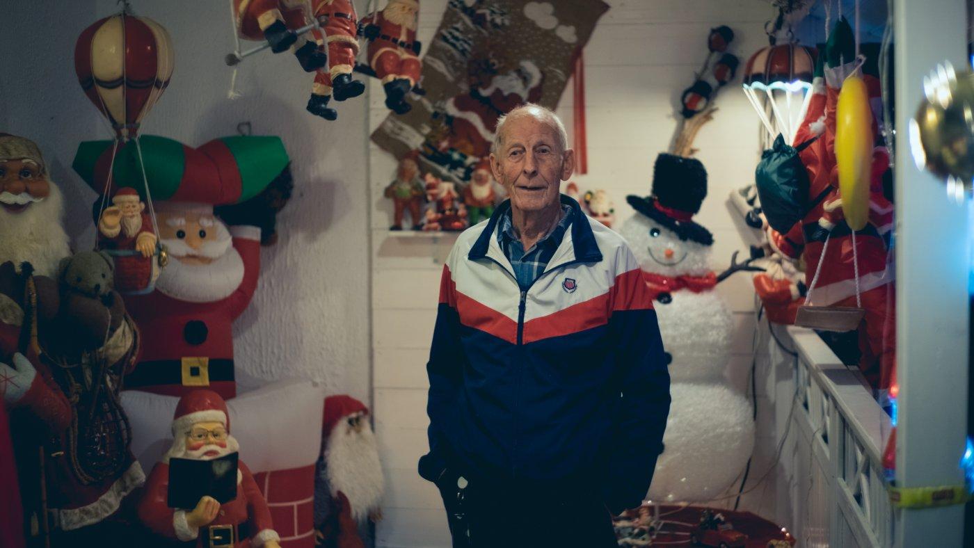 Tore Karlsen står ved inngangspartier til huset med en tynn sportsjakke på seg. I bakgrunnen ser man nisser, snømenn og juletrær i figurer som er hengt opp på veggen og lyser.