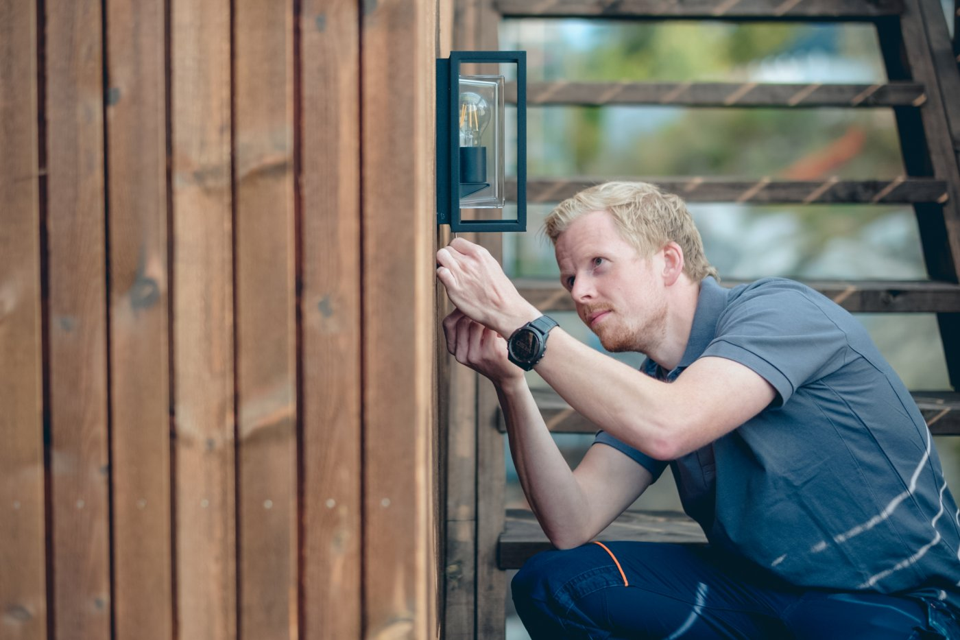 Ole-Magnus sitter på huk og lener seg inn mot ytterveggen av huset mens han skrur opp en utelampe på veggen.