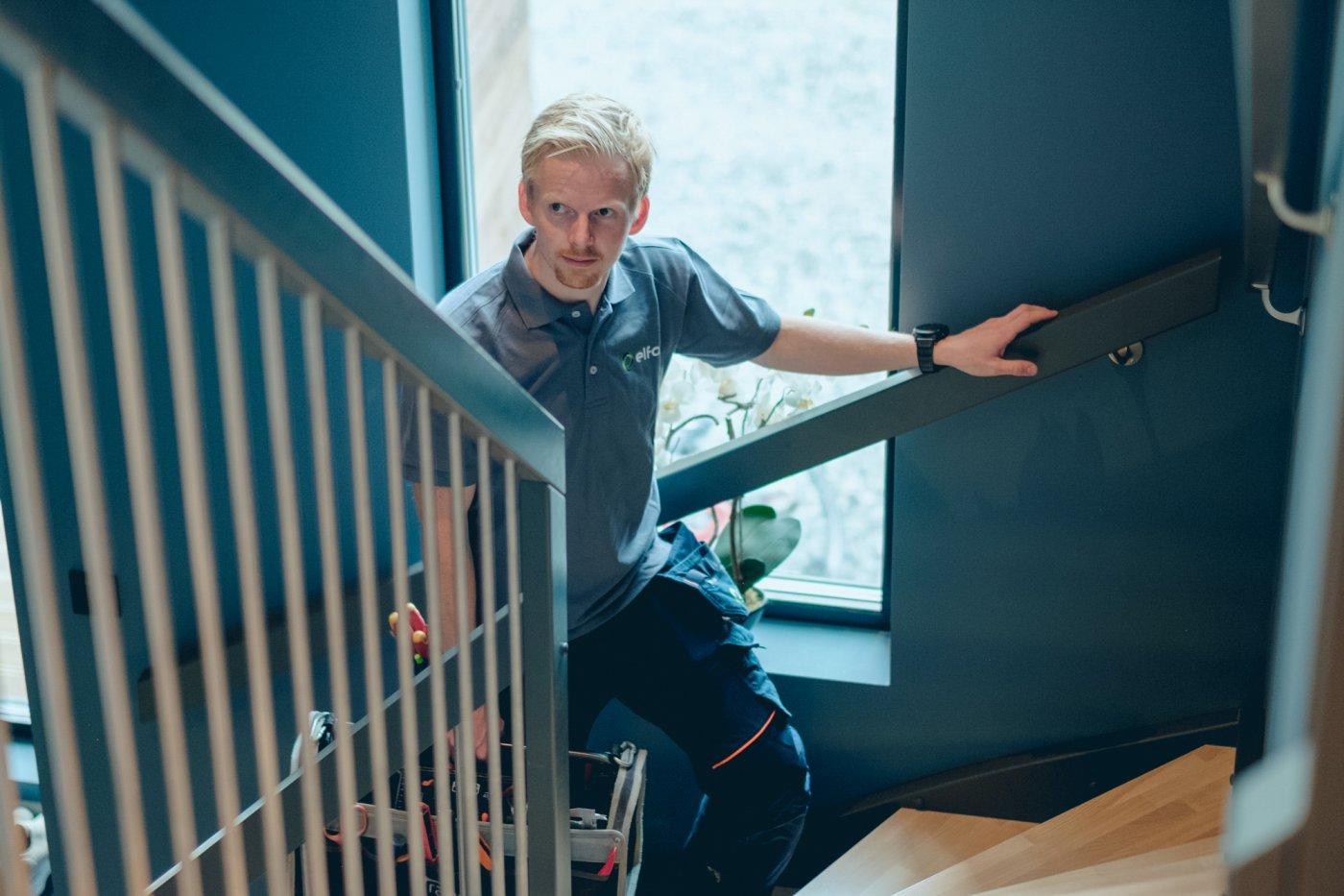 Ole-Magnus går opp en hjørnetrapp inni huset, og ser mot kamera. Han har verktøykasse i den ene hånden og den andre hånden på gelenderet på vei opp.