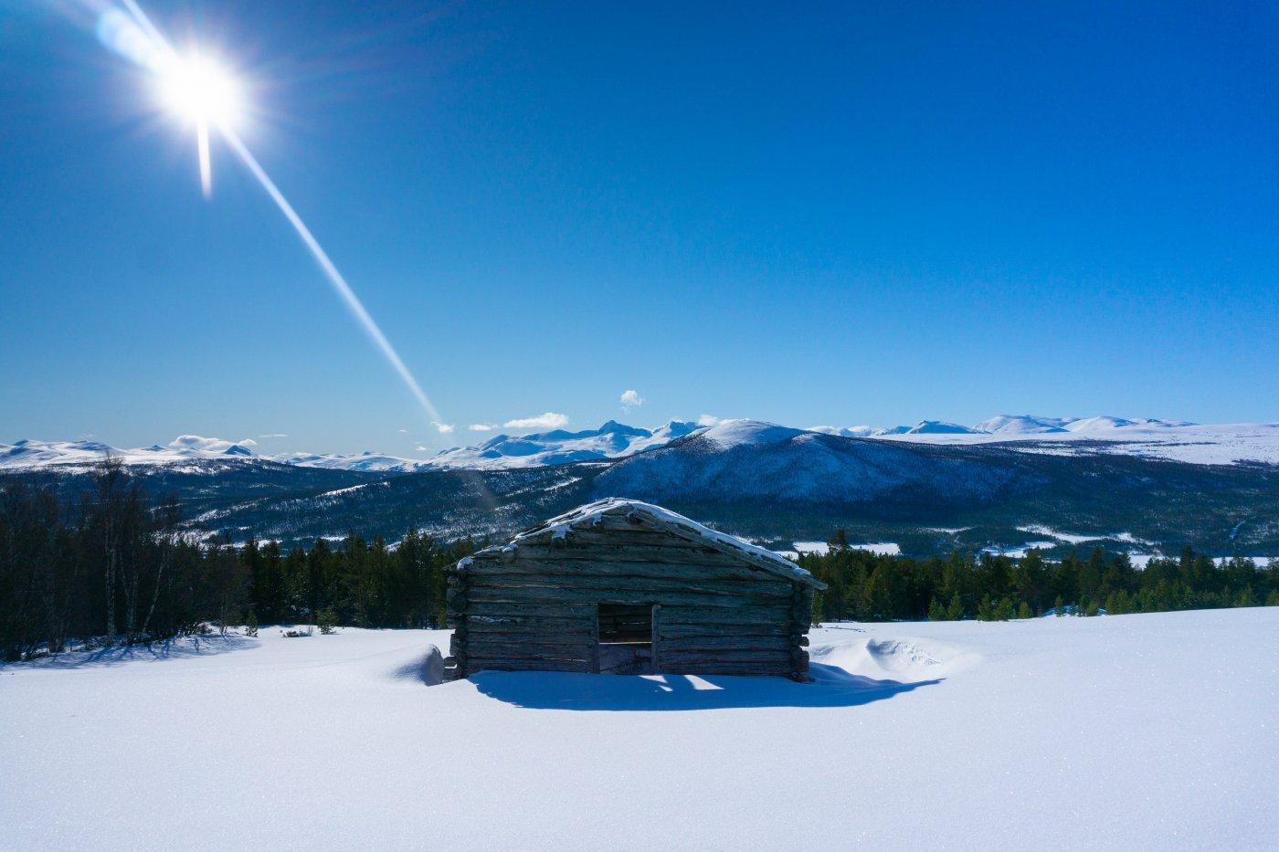 blå himmel, hvit snø og en liten urhytte i vinterlandskap