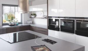 Stort og moderne kjøkken med hvit og brun innredning, tre ovner i ståhøyde, stor induksjonstopp og kjøkkenøy med nedfelte stikkontakter.