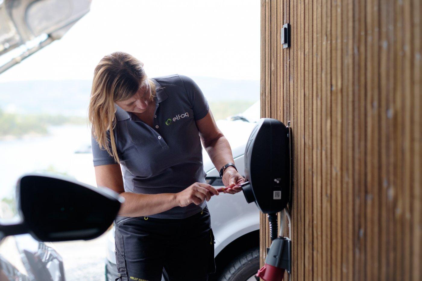 kvinnelig elektriker installerer sort elbillader på husvegg.