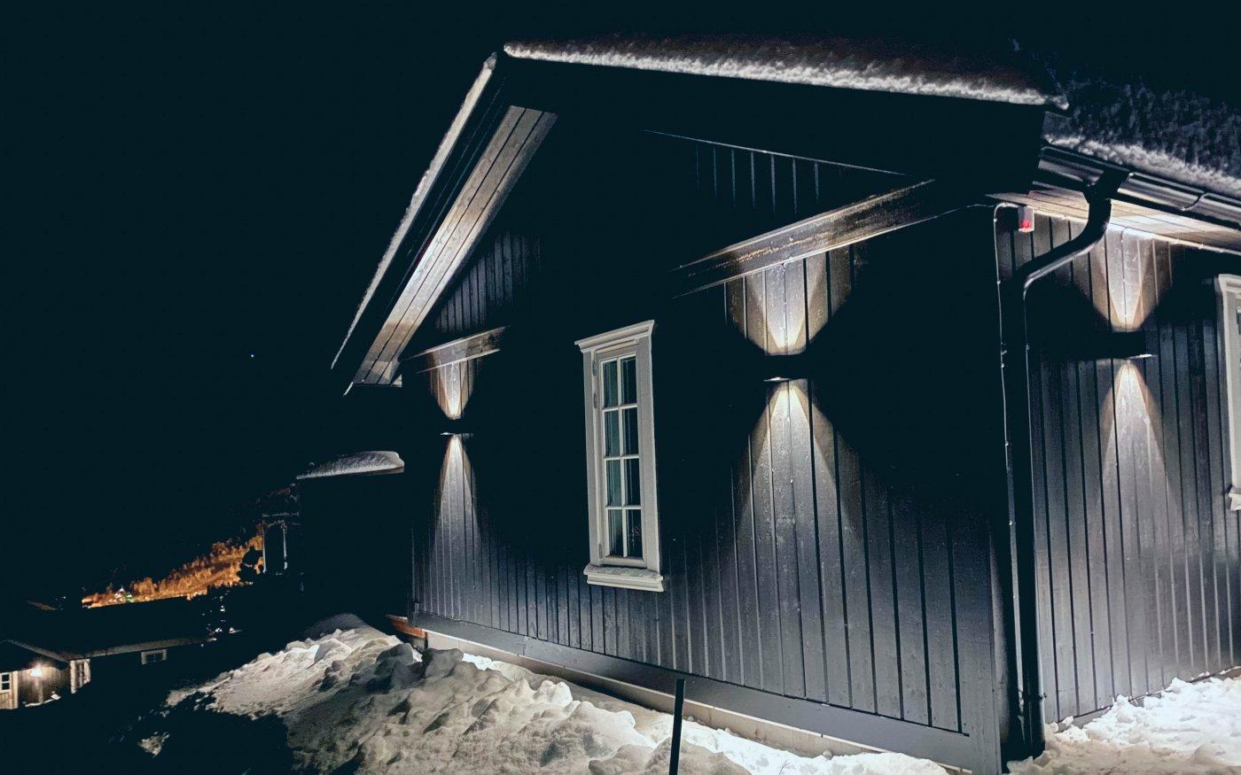 Sort hytte i vinterlandskap på kveldstid med sorte utelamper som lyser oppover og nedover.