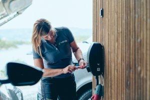 En Elfager monterer siste del av en elbillader på veggen i en garasje.