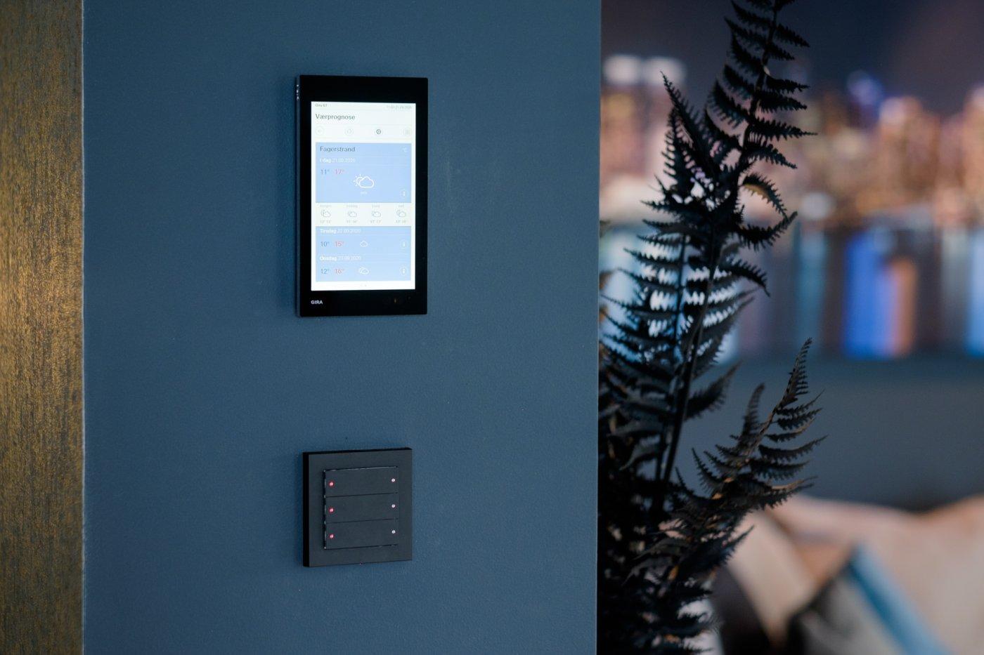 Sort betjeningsterminal med berøringsskjerm for smarthus montert på mørk blå vegg.