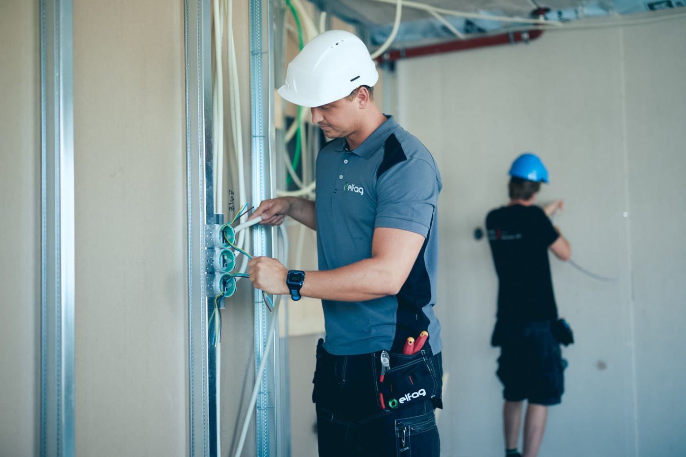 En Elfager er en byggeplass installerer diverse elektriske ledninger i veggen.