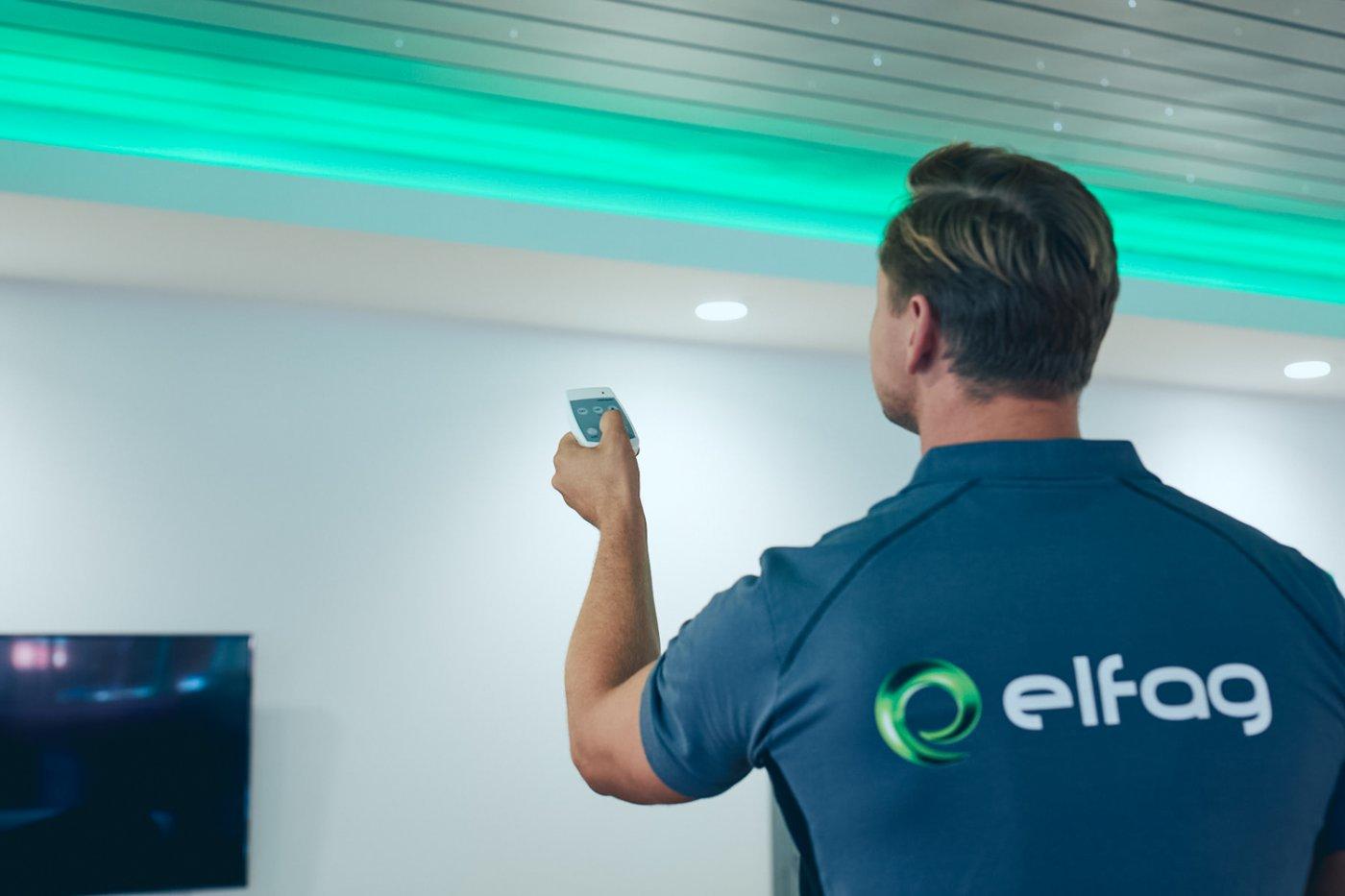 En Elfager bruker en app på smarttelefonen sin for å styre et grønt taklys.