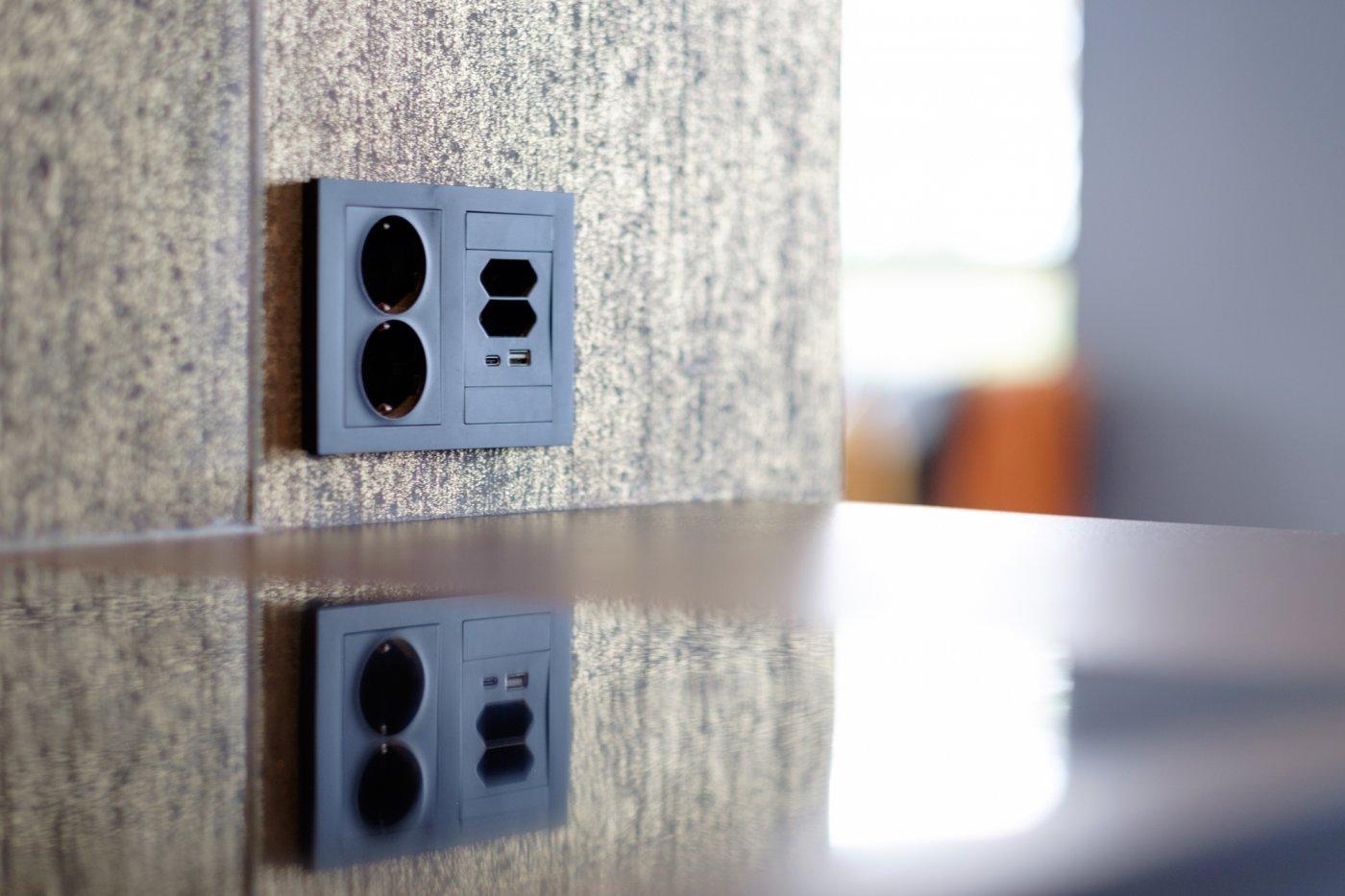 sort stikkontakt med forskjellige innganger og USB-port – montert over kjøkkenbenk.