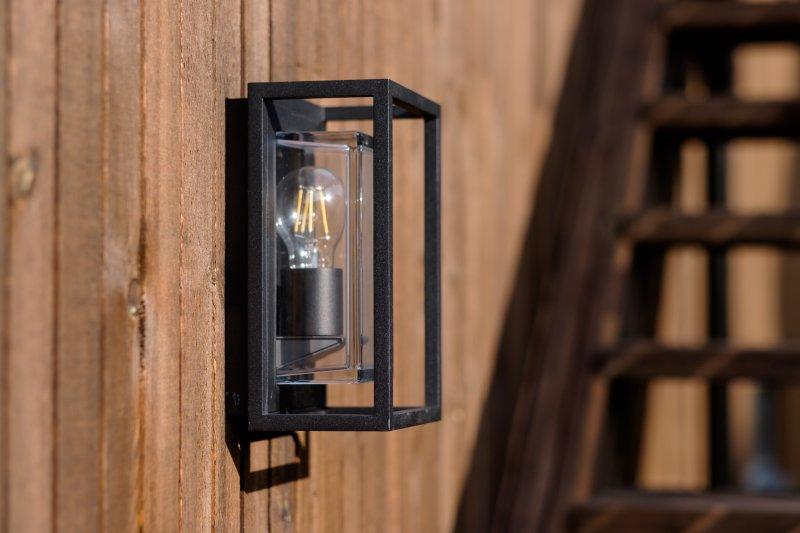Rektangulær utelampe med sort armatur og glassvinduer montert på brun husvegg.