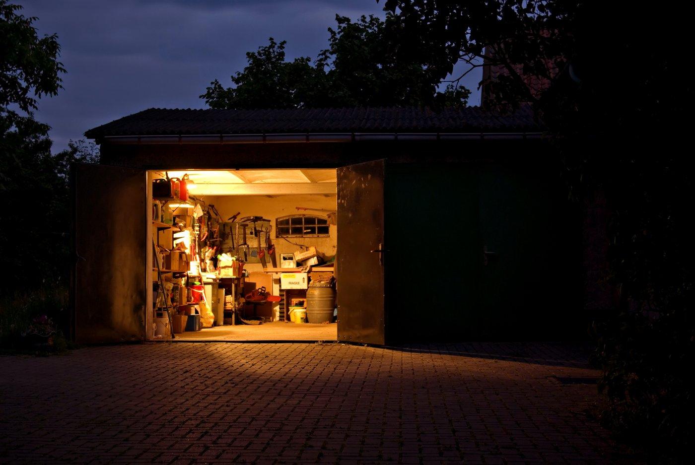Det er mørkt ute, men garasjen har porten åpen. Rommet er full av rot og bokser, men godt opplyst av lys i taket inne i garasjen.