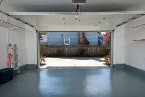 En tom innside av en garasje, med hvite vegger og åpen garasjeport i sentrum av bildet. En gardintrapp står lent inntil veggen på venstre side, og tomme hyller er montert på veggen på høyre side.