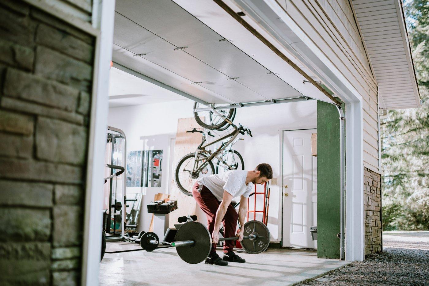 En mann trener i garasjen med garasjeporten åpen. Han løfter en vekstang, og i bakgrunnen henger det en sykkel på veggen, og ligger vektstenger på gulver.