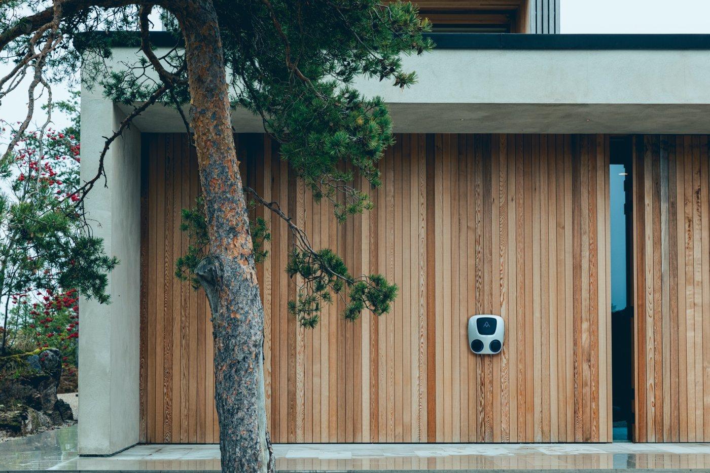 elbilladeren Charge Amps Aura med to uttak montert på moderne husvegg med betong og treverk i spiler.