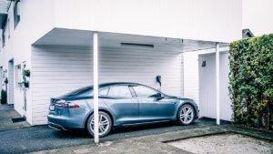 elbilladeren Easee Home montert i carport på hvitt hus med mørk grå elbil parker og koblet til lader.