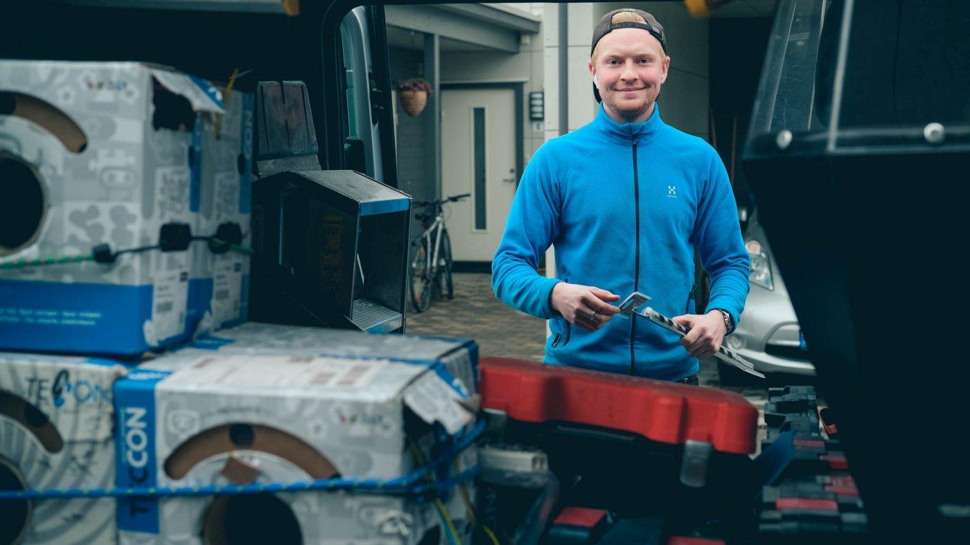 Elektriker Espen ser i kameraet mens han finner verktøy i arbeidsbilen.