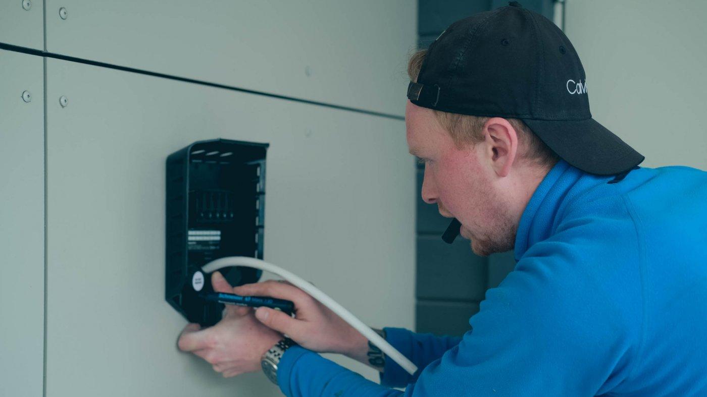 Elektrikeren lener seg inn mot elbilladeren på veggen og markerer punkter der den skal skrus fast på veggen.