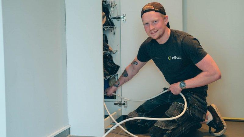 Elektrikeren sitter på huk og holder kabler som skal monteres inn i veggen mens han ser i kameraet.