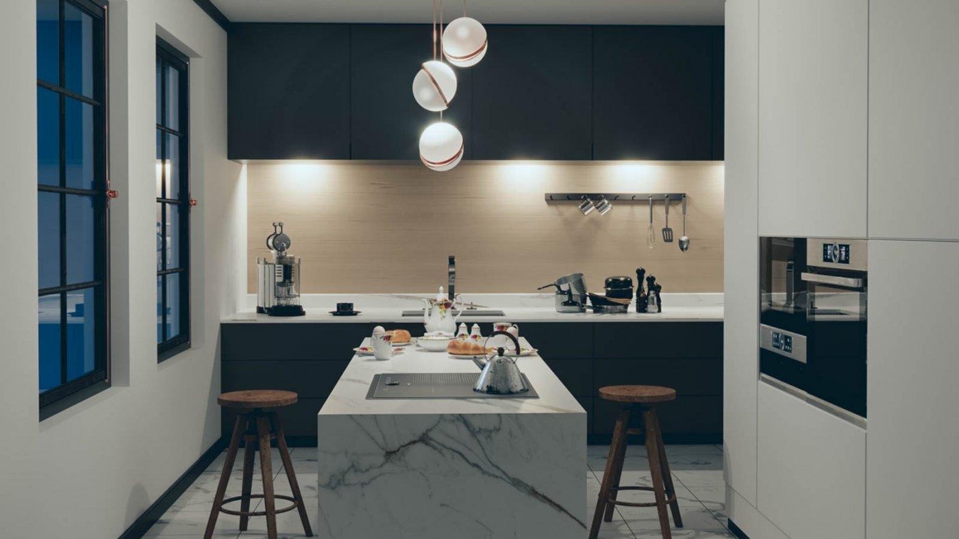 Mørke kjøkkenskap med kjøkkenøy i hvit marmor i forgrunnen. Dimmet belysning fra taklampene, og lys over kjøkkenbenken som lyser opp rommet.