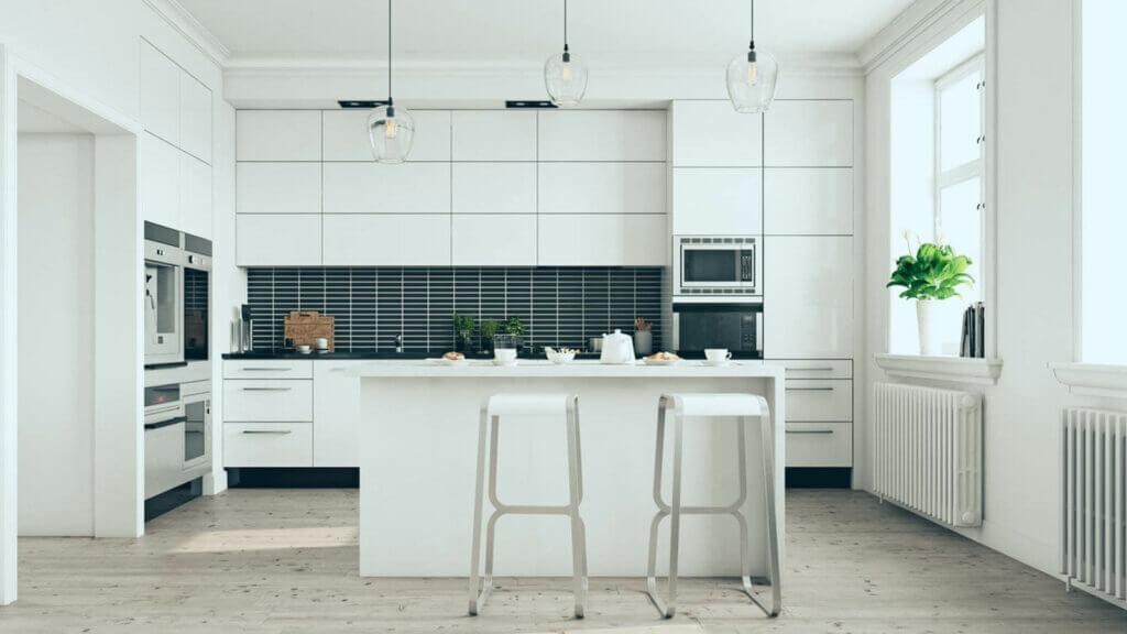 Et moderne, helhvitt kjøkken med skapplass fra gulv til tak, en kjøkkenøy og svarte backsplash-plater, i dagslys.